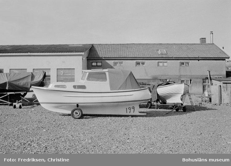 """Motivbeskrivning: """"Rolf Nicanders Båtbyggeri AB, på bilden båtmodellen Skäreleja, strax till höger därom snipa. I bakgrunden till vänster nyare verkstadslokal (byggd 1965), till höger äldre verkstadslokal."""" Datum: 19801003"""