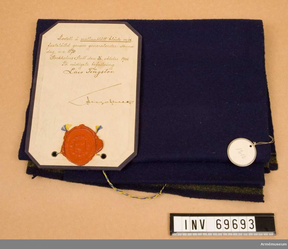 """På modellappen står skrivet: """"Modell å mellanblått kläde m/06, fastställd genom generalorder denna dag, n:r 1170. Stockholms Slott den 26. oktober 1906. På nådigaste befallning Lars Tingsten""""."""