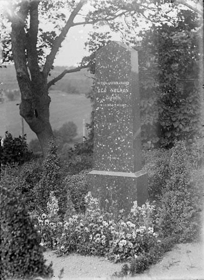 """Enligt senare noteringar: """"Svenskamerikanen Elo Nelsons gravsten på Foss kyrkogård. Elo Nelson ägde på sin tid Kvistrum, med såväl jordbruksfastighet som handelslägenhet, gästgiveri och tingshusbyggnad."""" (BJ)"""