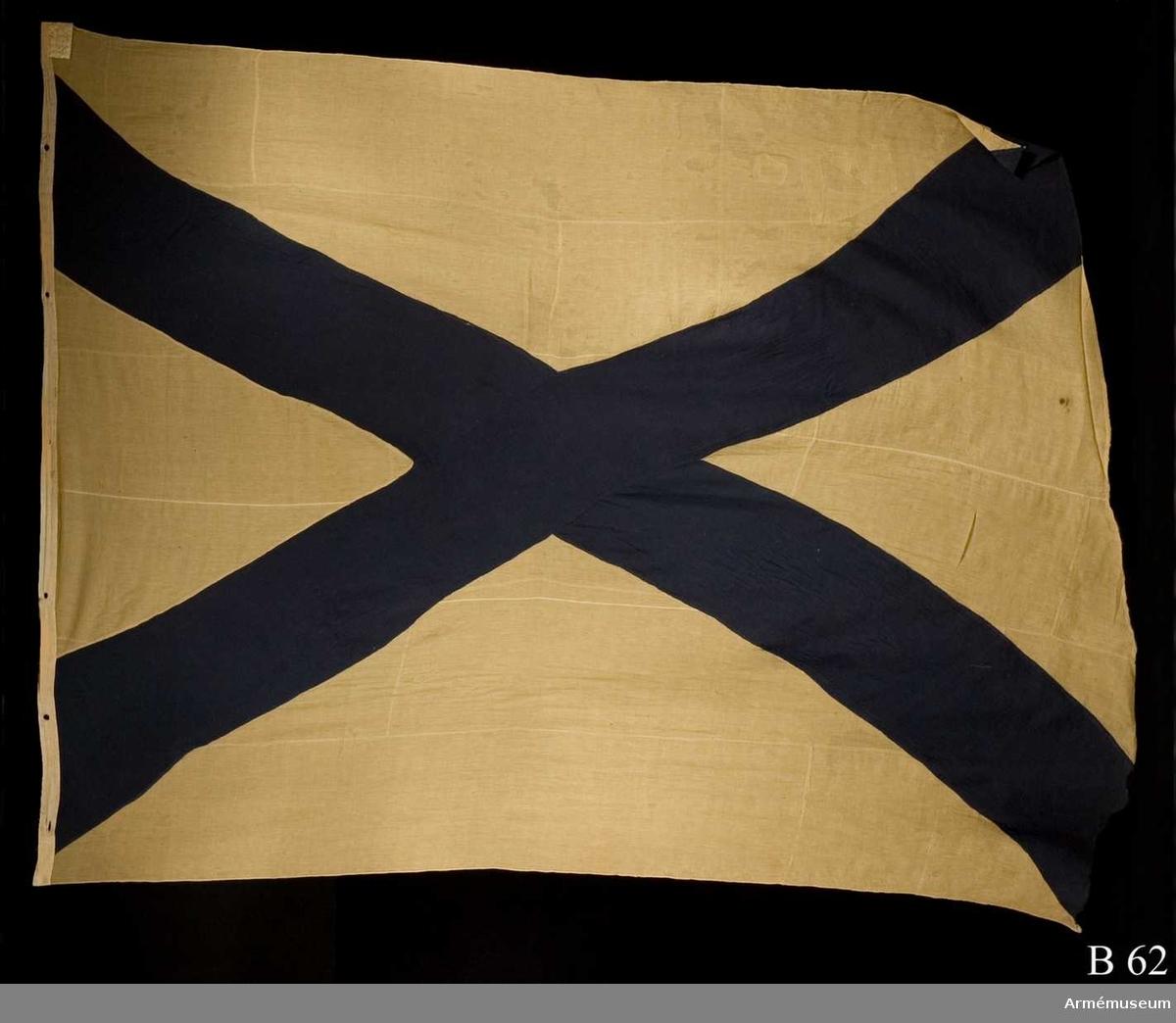 """Vit duk med infällt blått andreaskors. Lik av vitt linne med trensade hål. På flaggan är i övre stånghörnet en etikett av pergament fastsydd med texten: """"Denna ryska flagg, 6 duk, är tagen uti bataillen vid Svenskund under Hans Kungl Majts egit höga befäl och anförande den 9 julij år 1790. No 15""""."""