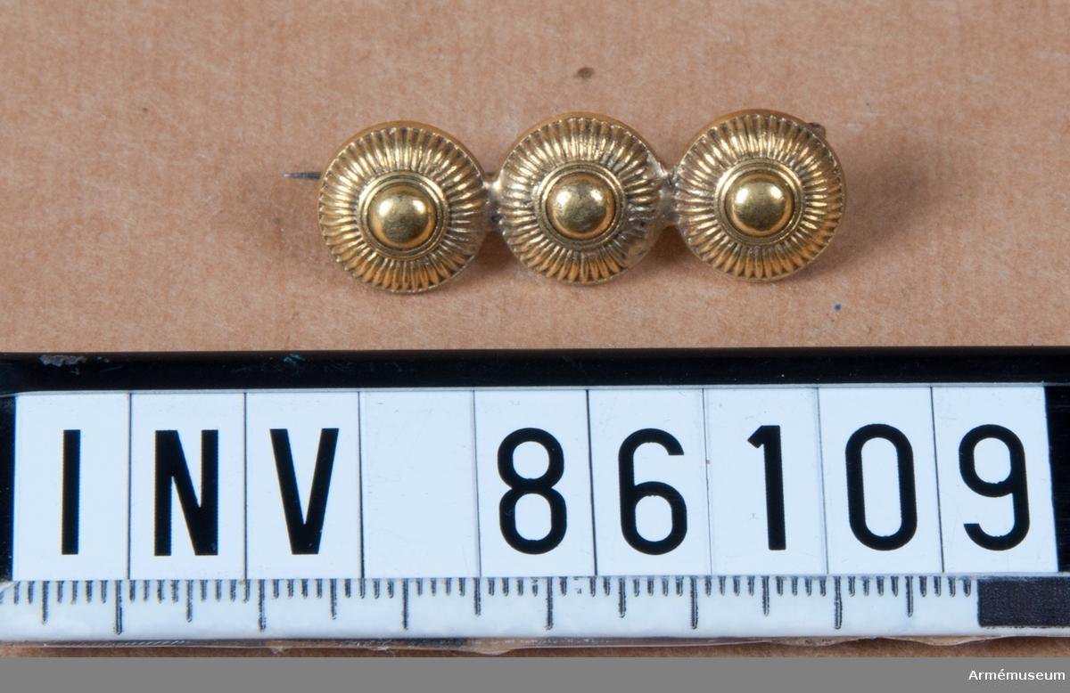 Grupp MV. Burna av Polly Nordahl d. 1965. Smycken utförda av artilleriknappar. A Brosch, 3 små artilleriknappar.