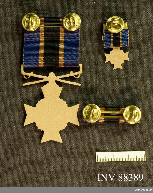 Tre samhörande föremål; en minnesmedalj, en minatyrmedalj och ett släpspänne. Bandet kluvet i blått, svart och blått med gula streck mellan fälten.