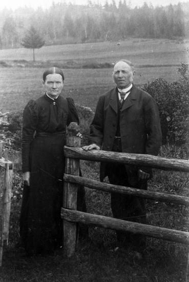 Äldre par vid grind i jordbrukslandskap