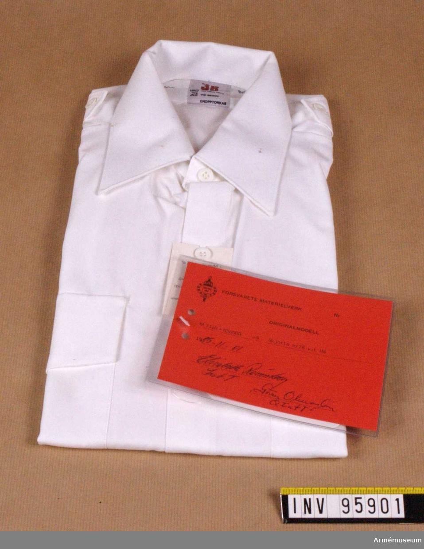 """Skjorta med hel, fast krage och ok av dubbelt tyg. Skjortan har bröstfickor med lock som knäpps. Fasta axelklaffar, bredd 42-45 mm, utan axelklaffshylsor. Kort ärm. Skjortan är avsedd för alla uniformsdräkter inom försvaret där vit skjorta är tillåten. Vidhängande etikett: """"Försvarets materielverk Originalmodell M 7320-056000-4, Skjorta m/78 vit HÄ, 1985-11-01 Elisabeth Rönnberg Int T / Göran Olmarker Q Int T""""."""