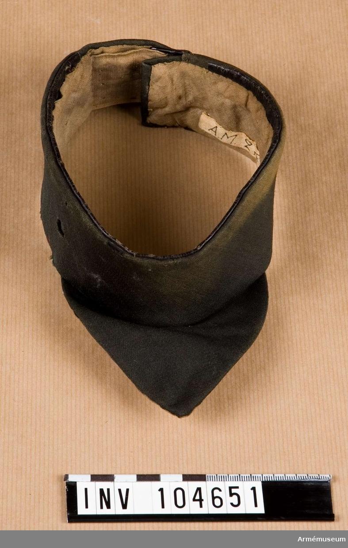 Grupp C I. Fastställd modell 1854 halsduk go 30/12 1854           Halsduk, svart, med smal läderkant och fodrad med grått, tuskaftad bomull.