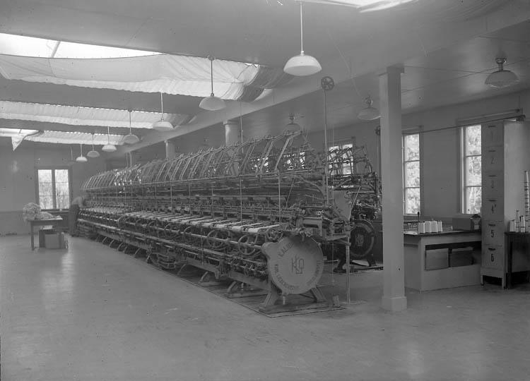 """Text till bilden:""""Fabrikslokal med maskiner. En man håller på med arbete längst ner i lokalen. I taket reglerbara gardiner. Damstrumpor""""."""