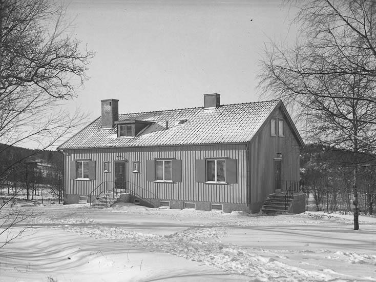 """Text till bilden:""""En villa med snötäckt gårdsplan. Kamratgården""""."""