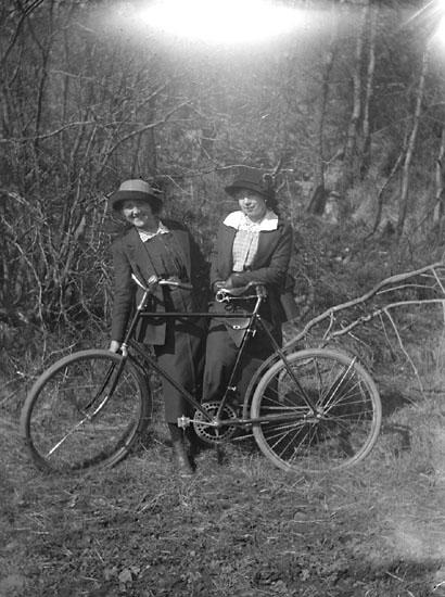 """Enligt senare noteringar: """"Ester Helgesson, Ingrid Olsson. Taget mitt emot Folkets park. (med cykel), 19/4 1914."""""""