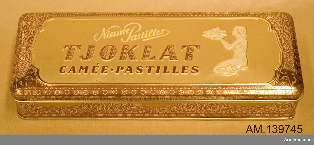Chokladask i plåt av märket Nieuwe Pastilles. Guldfärgad med snirkliga mönster i rött. Prydd med en kvinna som håller fram ett serveringsfat. Innehåller ett vitt pappersinlägg med liknande kvinnomotiv och två  helbruna, samt en papperslapp med noteringar om vad som tidigare ska ha förvarats i lådan.