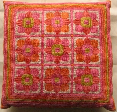 Två stycken stoppade kuddar. Broderad i tvistsöm med lingarn. Nio blommor i rutor. Randig bård runt om.  Kudde nr. 1551-1 är sydd i rosa, orange, och rött. Kudde nr. 1551-2 är sydd i blått, grön och orange.