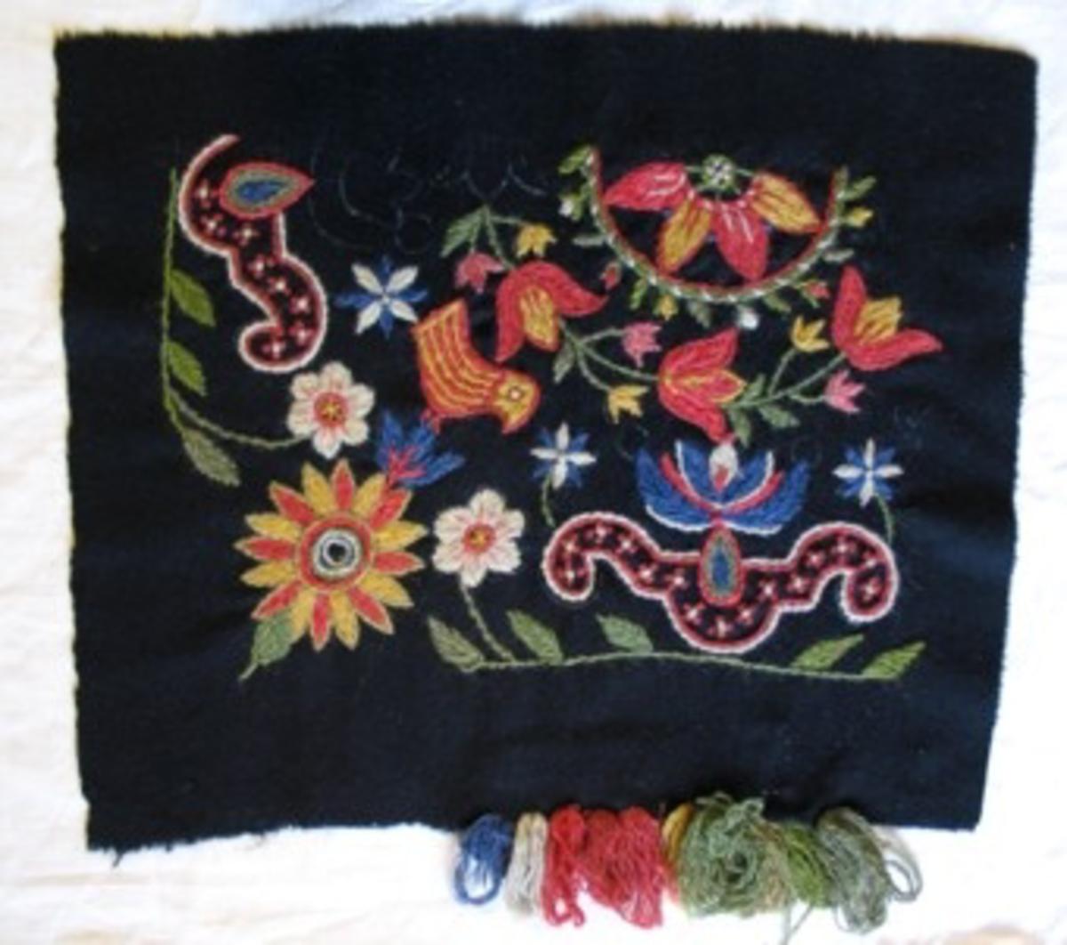 """Yllebroderiprov broderat på ylletyg med löstvinnat tvåtrådigt ullgarn. Två nyanser tvinnade samman. Tofsar av garnprover fästade vid ena kanten: 4 gröna blandningar, 1 gul, 3 röda, 1 naturvit, 1 blå. Troligen 1/4 av ett kvadratiskt broderi uppbroderad: 8-flikig blomma i cirkel i centrum, krans med tulpaner utanför. Urna med blomma på sidorna, hörnet en större blomma, varpå en fågel sitter. Äldre märkning baktill på påsytt band: """"GÄRDS HÄRAD, KAT. N:r 7, PL. N:r 1220""""."""