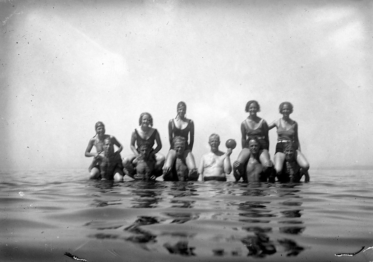 Några ungdomar badar i sjön, en man håller i en boll för vattenlek.