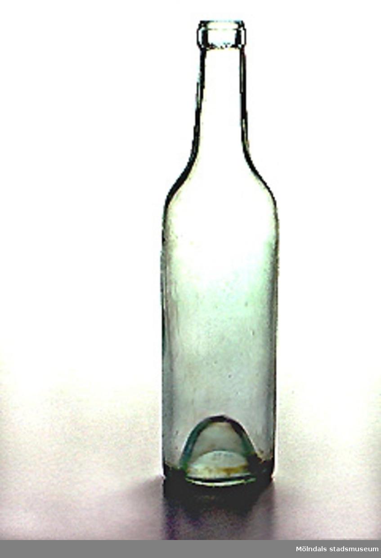 Brännvinsflaska i klart glas, med rejält konkav botten. Smutsig på insidan.