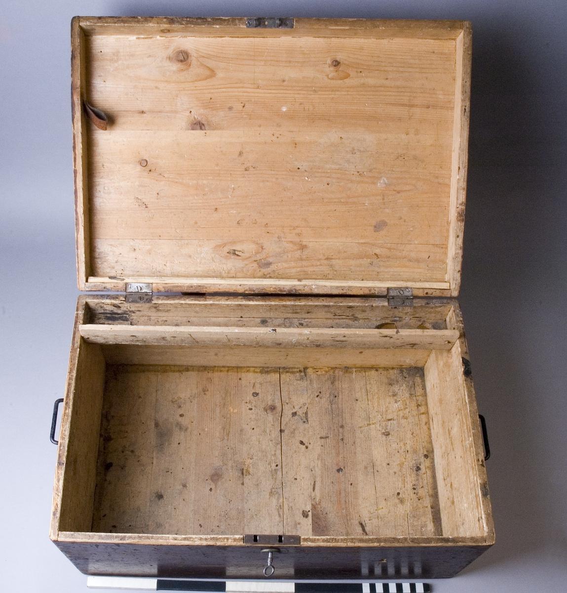 Kista A med nyckel B. Kista av trä, med sinkade och limmade hörn, målad i en brun kulör. Kistan har enkla bärhandtag i metall på kortsidorna samt ett fabriksgjort instickslås med rund nyckelbricka. Baktill, inuti kistan finns ett längsgående fack med två hål, troligtvis för verktyg. På insidan av locket finns en läderstropp som troligtivs är för verktyg. Nyckel, fabriksgjord, av metall, med enkel utformning.