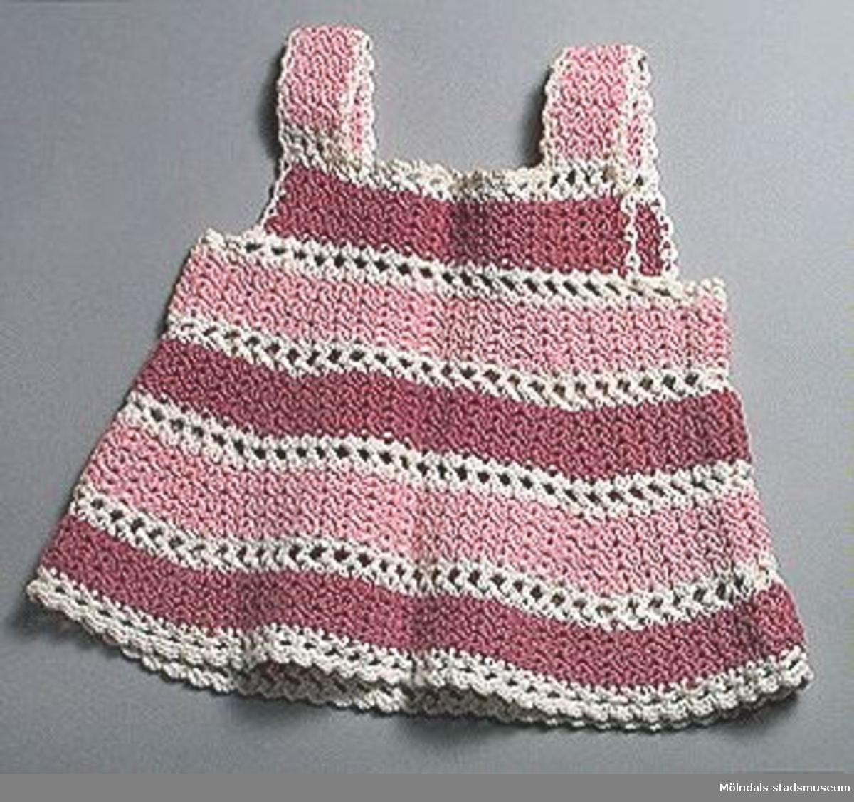 Barnklänning, virkad randig i mörkt och ljust, rosa samt vitt.