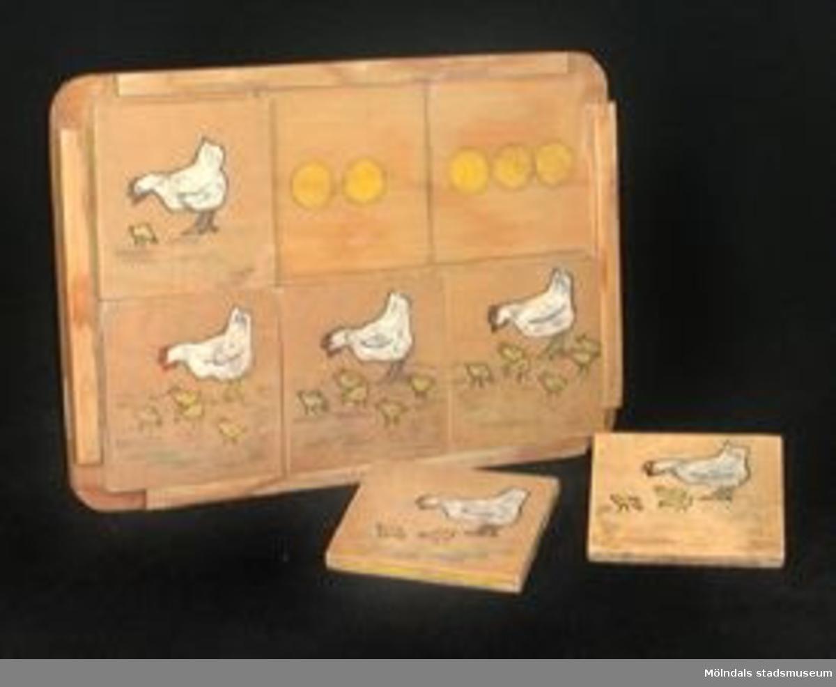 """Handmålat träpussel i sex delar, avsett för att lära sig räkna. Antal gula prickar på brickan skall stämma in på rätt bild bland pusslet. Bilderna föreställer en höna med ett antal kycklingar på varje pusselbit. Baksidan är märkt med siffran """"215"""" (på en tejpbit i blå tusch) och initialerna """"M.B"""" i grön tusch.Tidigare sakord: leksak."""
