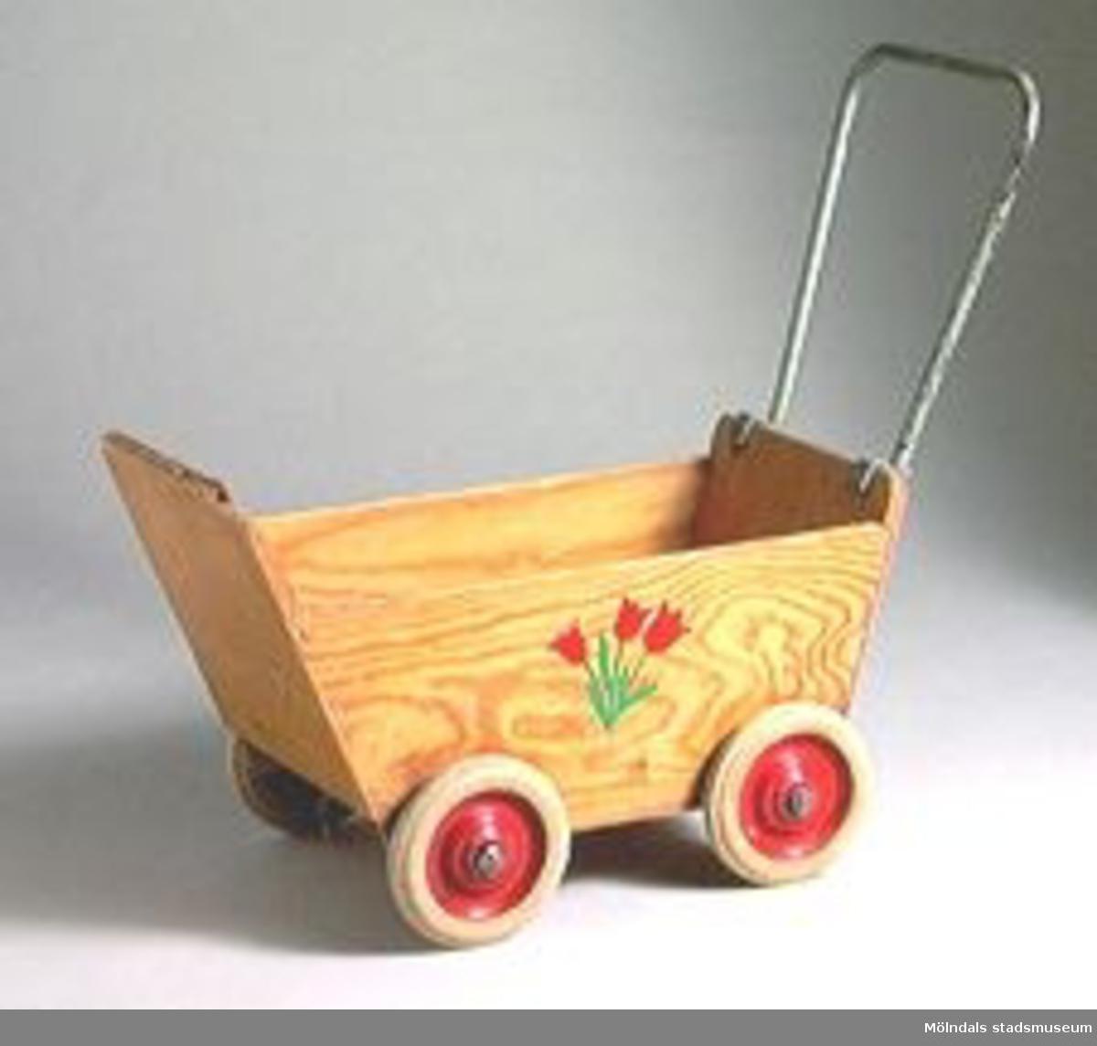 Dockvagn med fyra st. hjul, tulpaner dekormålat på sidorna.Ingår i Holtermanska samlingen. Tillstånd vid förvärv: skadad i ena hörnet.
