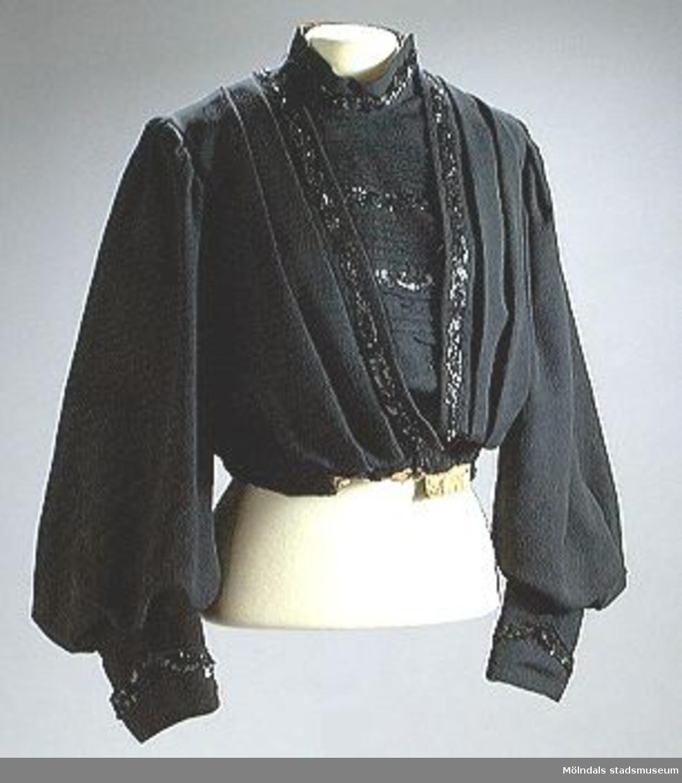 Svart blusjacka med helt bröst och liten ståkrage. pösiga ärmar.Påsydda paljetter på bröst, krage och på ärmens nederkant.Tvärsydda veck på bröst, längstgående sydda veck på ryggen.Gult linnefoder. Knäpps med hyskor och hakor.Hör troligtvis ihop med en kjol.Hemsytt.