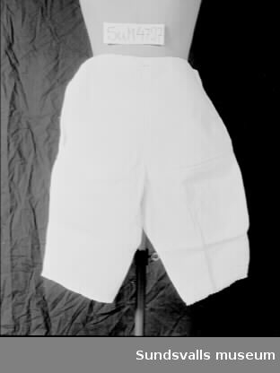 Benkläder i vitt bomullstyg. Sprund i var sida som knäpps med en knapp. Nederst på benen två lagda veck, samt brodyr med hålsöm och uddkant.