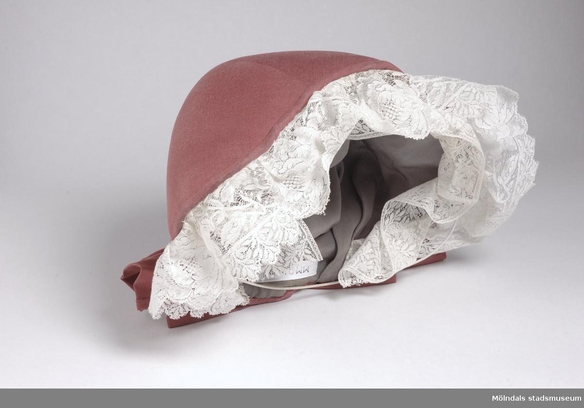 Liten röd damhatt. Spetskantad runt ansiktet. Stor rosett bak. Fodrad med grått sidentyg.Det finns också tillhörande kjol och väst. MM04099, MM04100.