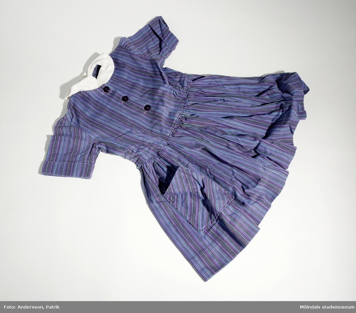 Flickklänning av lilafärgat randigt bomullsyg. Vid kjol, rynkat i midjan en ficka fram, påsytt vit krage.