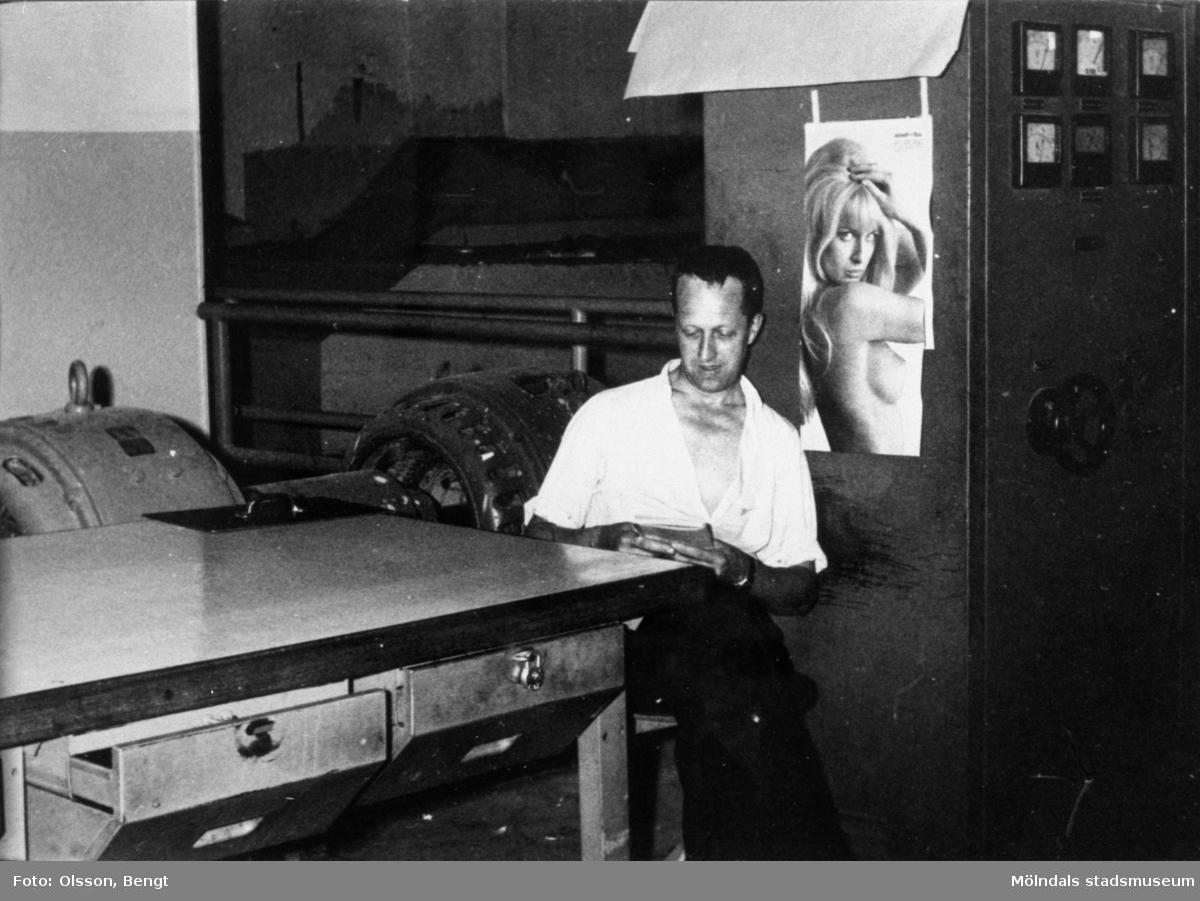 Maskinförare Kurt Floman läser vid förarbordet PM 10 på Papyrus i Mölndal år 1962. Till höger manöverskåpet. Affisch med kvinna på väggen.