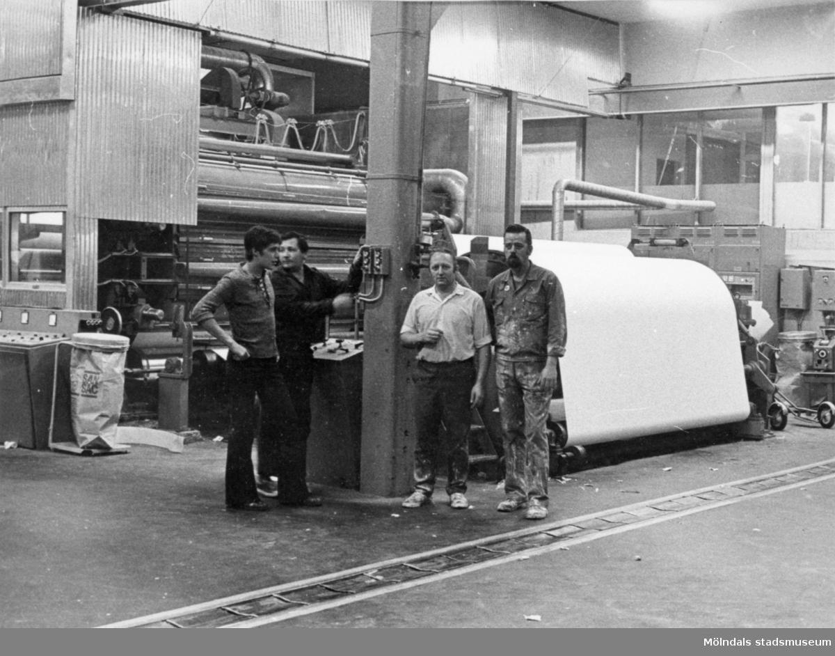Fyra pappersarbetare står framför en pappersmaskin på Papyrus, cirka 1960- till 70-talet.  Mannen som står längst till höger heter Stig Samuelsson.