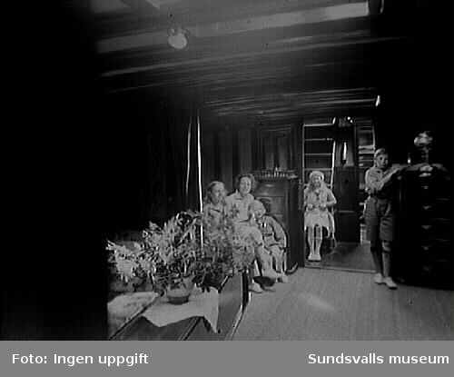 """Kvinna med fyra barn  i segelbåten """"Allonas"""" kajuta. Förmodligen familjen Norströms barn. """"Allona"""" beställdes av Wilhelm Bünsow, med Lennart Norström som senare ägare. Hon byggdes 1899 på Stockholms Båtbyggeriaktiebolag, troligen ägt av August Plym. Konstruktören var ingenjör Axel Nygren.Längd över allt, l ö a, var 26 meter, längd efter vattenlinjen, l v l, 19 meter, bredd 5,20 meter, djupgående 3,70 meter. Deplacementet var på 9 ton. Segelarean omfattade 300 m2 (375 m2 ursprungligen, före omriggning). Båten var utrustad med gaffelrigg, bermudasrigg, mesanmast (för att sätta segelmängden lättare?). I kajutan fanns sex kojer, i chefshytten och i styrmanshytten vardera fyra kojer, samt tre kojer i skansen."""