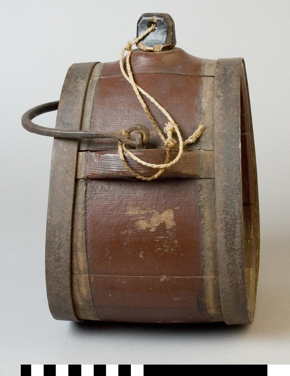 """Mjölkflaska av trä, målad brun. Med band och handtag av järn. Med tillhörande propp av svartmålat trä.  Märkt på ena sidan 1883, i vitt. Märkt på andra sidan """"JMS"""", i vitt."""