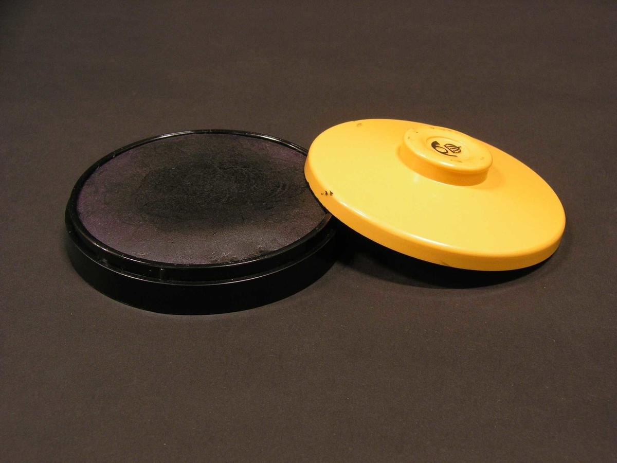Cirkelformad plastdosa med lock med ilagd tunnare filtskiva. Locket är försett med en svart postsymbol.