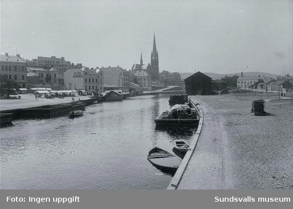 """Selångersån med bruksbåtar. Vid Fisktorget bedrivs torghandel.I bakgrunden finns två husfasader med synlig text var av den ena lyder BLOMS JERNHANDEL.Bildtext i fotoallbum""""Vy från Norrmalm""""."""