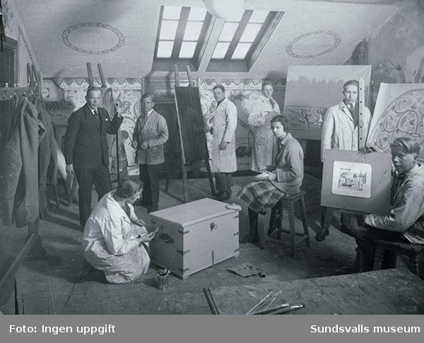 Gustaf Walles (stående i kostym till vänster) lärare för dekorationsmåleri vid Sundsvalls yrkes- och lärlingskola, tillsammans med sina elever. Walles var lärare på skolan från 1929 till 1965.