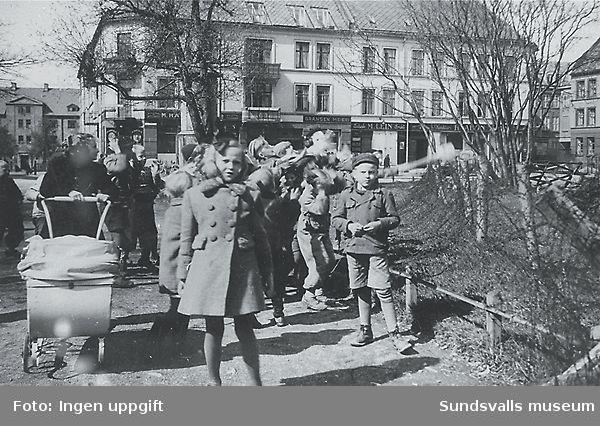 """""""Borna får sjokolade av """"Svenskehjelpen"""" Lademoen."""" (Bildtext i fotoalbum. Ägare Emil Tessem, Steinkjer.)Trondheim i maj 1945."""