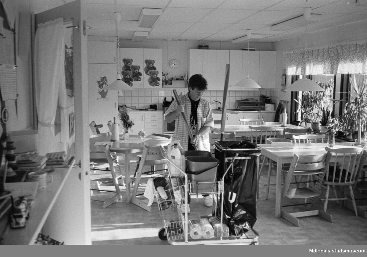 En kvinnlig personal, iklädd städrock, svabbar köksgolvet vid Katrinebergs daghem. Framför henne står en tidstypisk städvagn. I köket står flera bord med trip trap stolar och vanliga stolar.