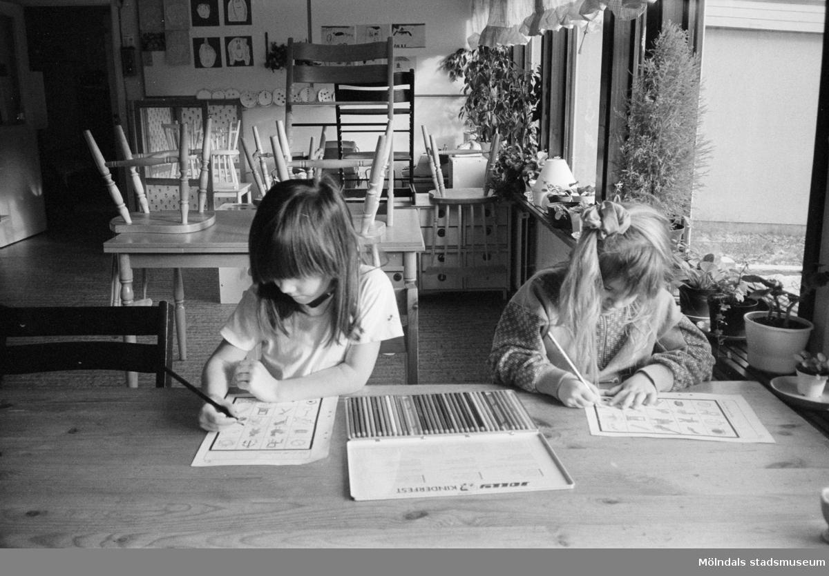 Cecilia och Jessika sitter vid ett bord och färglägger med hjälp av färgpennor, förtryckta figurer på var sitt A4-blad. Båda är mycket koncentrerade. Lunkentussen, Katrinebergs daghem 1992.