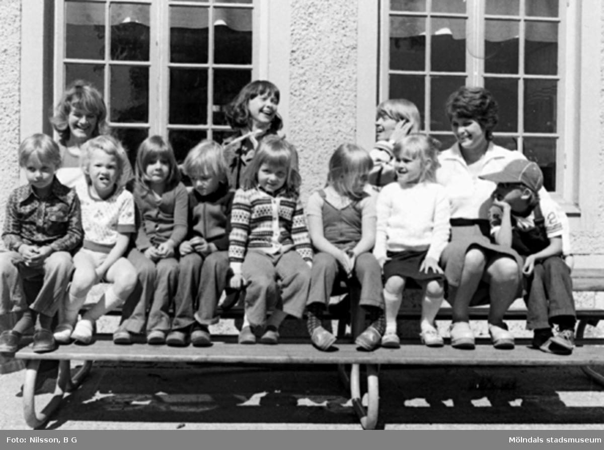 Barn och fröknar som sitter på en bänk utomhus. Holtermanska daghemmet, okänt årtal.