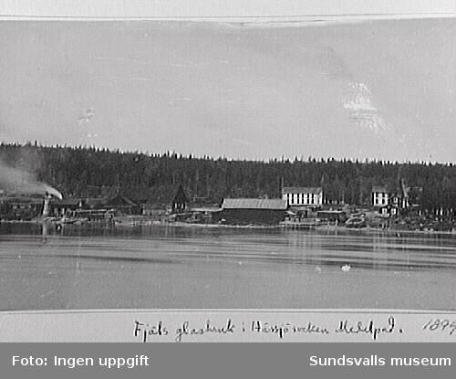 Fjäls glasbruk, Hässjö. Till vänster ses hytta och sliperi, i mitten lagerbyggnaden samt båtbryggan och i bakgrunden det vita tvåvåningshuset där arbetarna bodde. Den vita byggnaden t.h. inrymde vid denna tid i den övre våningen patron Johan Fredrik Gauffins bostad samt kontor, i bottenvåningen bodde bokhållare A. N. Törnberg samt glasarbetarna Fredrik Forsberg, C.J. Skjöld och J.H. Lindeman.