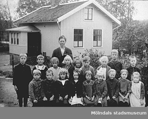 Bild ur album som tillhört Ingrid Larsson, Bölet. Det är hennes skolklass utanför skolan i Livered, Kållered. Småskollärarinna Hulda Holmén. Hembygdsföreningen har förtecknat resten av klassen.