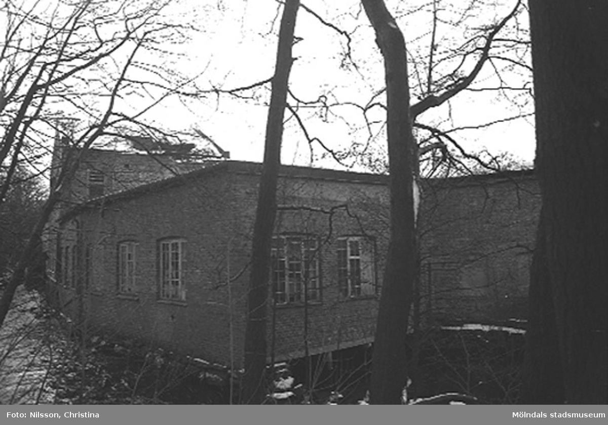 Fabriksbyggnad i tegelsten vid vattendrag.