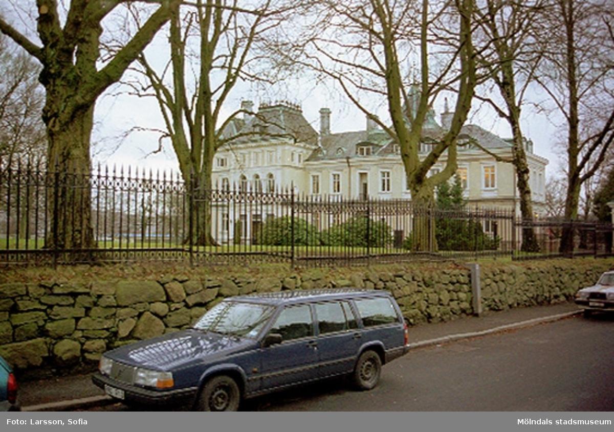 Vy från Kvarnbygatan mot Villa Papyrus som skymtar i bakgrunden. I förgrunden ses en parkerad mörblå Volvo-kombi som står utefter en trottoar och Papyrus stenmur. Ovanpå muren finns ett stängsel och innanför ses höga träd.