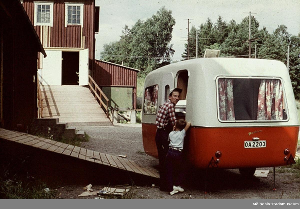 Kontroll av färdig husvagn.Bilderna är tagna våren/sommaren 1960, ungefär där nu Almåsskolans slöjdsal är belägen i Lindome. Fabriken ägdes tidigare av Colldéns möbler. Fabrikslokalerna ägdes sedan av Hj. C. Samuelsons AB, som tillverkade i huvudsak butiksinredningar till Åhlen & Holms varuhus. Vid årsskiftet 1959-1960 flyttade Samuelson tillverkningen till Floda. Fabriken övertogs av AB Lamellplast, ett företag inom Persöner koncernen, Ystad. AB Lamellplast  tillverkade båtar och en husvagnstyp av glasfiberarmerad polyesterplast. Plastmassan levererades av SOAB Mölndal.