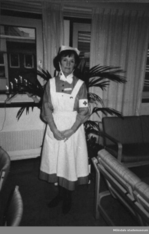 """Ingrid Petersén iklädd sin sjuksköterskeuniform, cirka 2004.Hon invigdes till sjuksköterska från Röda Korsets sjuksköterskeskola i Stockholm den 14 oktober 1958 av grevinnan Estelle Bernadotte utav vilken hon erhöll i sin hand den brosch som är så signifikant för Röda Korsets sjuksköterskeskola.Vid 18 års ålder fick man börja på Svenska Röda Korsets sjuksköterskeutbildning. Då blev eleven antagen till 3 månaders provtjänstgöring den s.k """"plättperioden"""". Under denna tid användes en liten mössa till arbetsuniformen som man fick vid utbildningens början. Den lilla mössan avvek från den ordinarie mössan för att visa att eleven gick på prov. Efter provtjänstgöringen fick eleven veta om hon godkändes för vidare utbildning på 3,5år. Efter 2 års studier fick eleven bära den vita armbindeln och blev därmed undersköterska.Arbetsuniformen var skräddarsydd och bestod av en blå bomullsklänning, ett vitt förkläde som knäpptes i kors i linningen med särskilda manschettknappar och en vit mössa. Klänningens längd skulle vara ett visst antal centimeter ovanför golvet och förklädet skulle vara ett visst antal centrimeter ovanför den nedersta klänningsfållen. Man fick endast använda svarta strumpor och svarta skor eller bruna strumpor och bruna skor till klänningen.Till klänningen hörde också en vit krage till som fastsattes med knapp baktill och  med sjuksköterskebroschen framtill. Till klänningen fanns ett särskilt bälte som gjorde att förklädet inte skulle vika sig i midjan. På vänster ärm fastsattes den vita armbindeln som visade att det var en Röda Kors syster! Den vita mössan var enligt ett mönster särskilt för Röda Korsets sjuksköterskor (varje sjuksköterskeskola hade sin egna design av mössan). Endast nålar med pärlhuvud fick användas på mössan. På mössan fästes hakrosetten. Vid utomhusvistelse fick man bära den tillhörande svarta kappan. Den skulle vara längre än klänningen. Till kappan var man tvungen att använda svarta strumpor och svarta skor och sätta fast den vita armbind"""