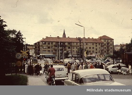 Vid järnvägsövergången i Mölndals centrum. Järnvägsbommarna över Kvarnbygatan var ofta nedfällda. Dels gick många tåg på Västkustbanan, dels växlade man vagnar och körde in dem på Papyrus industriområde. Kvarnbygatans viadukt Mölndalsbro var färdig 1975, då försvann bommarna och bil- och gångtrafikanter behöver inte längre vänta för att ta sig till centrala Mölndal.