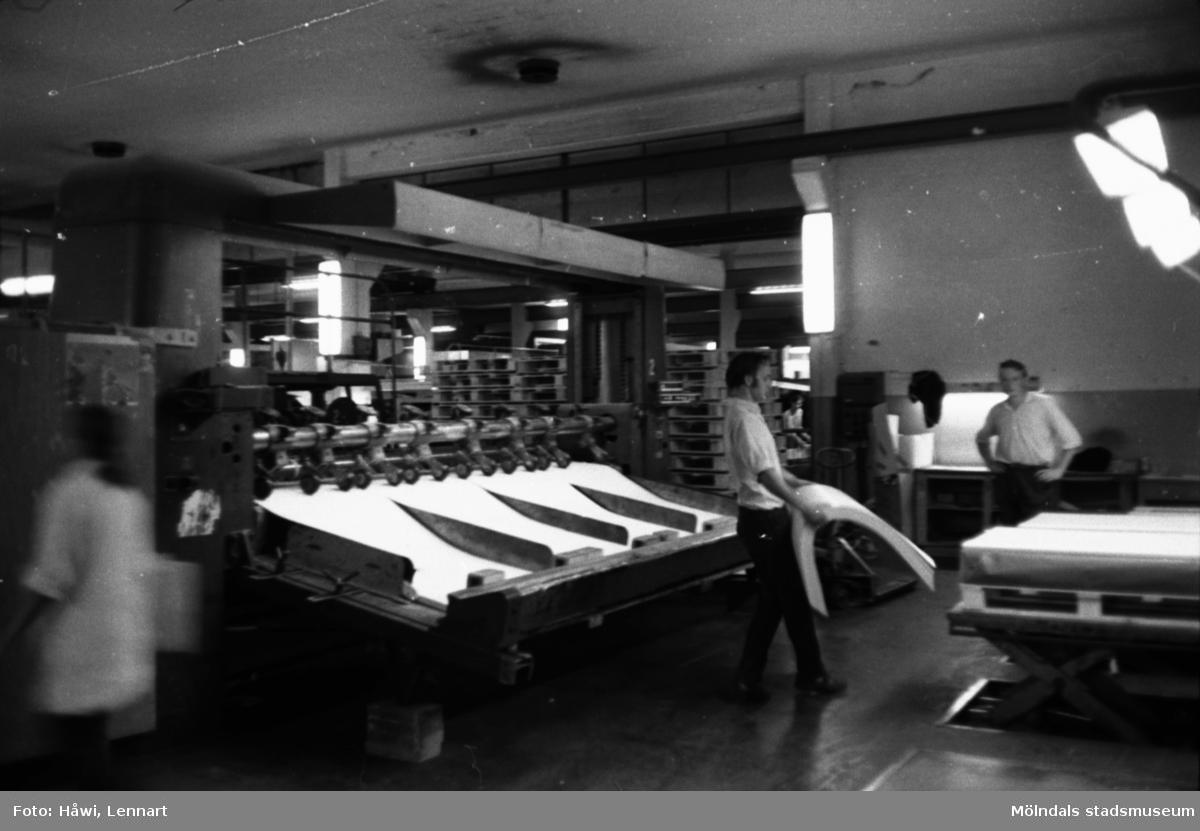 Män i arbete vid maskin, KM 2 klipp. Lyfter över bunten med kartong. Lägger kartongbuntarna på en pall. Arbetspassen var c:a en halvtimme, det var ett tungt arbete och man orkade inte hålla på under längre pass. Byggnad 6, Papyrus i Mölndal, hösten 1970.