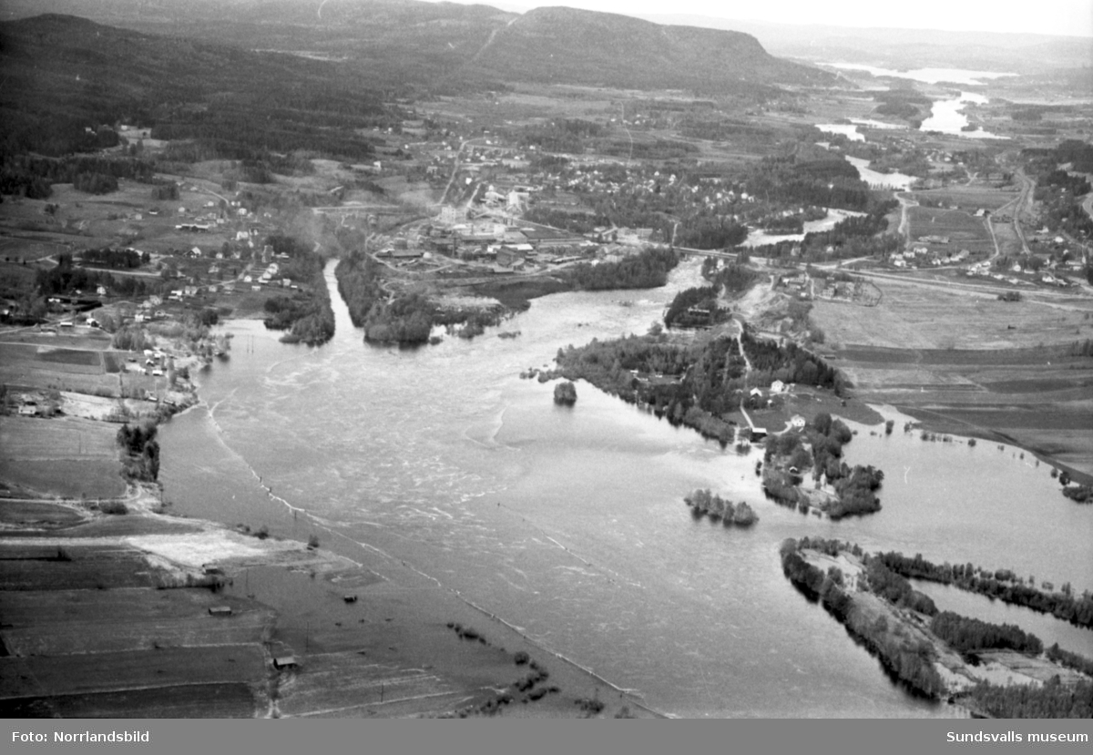 Flygfoton över Ljungans dalgång med högt vattenstånd och översvämningarna på grund av vårfloden efter den snörika vintern 1966. Träd, hus, bodar och vägar under vatten i Stöde, Viskan, Torpshammar, Fränsta och Ljungaverk.