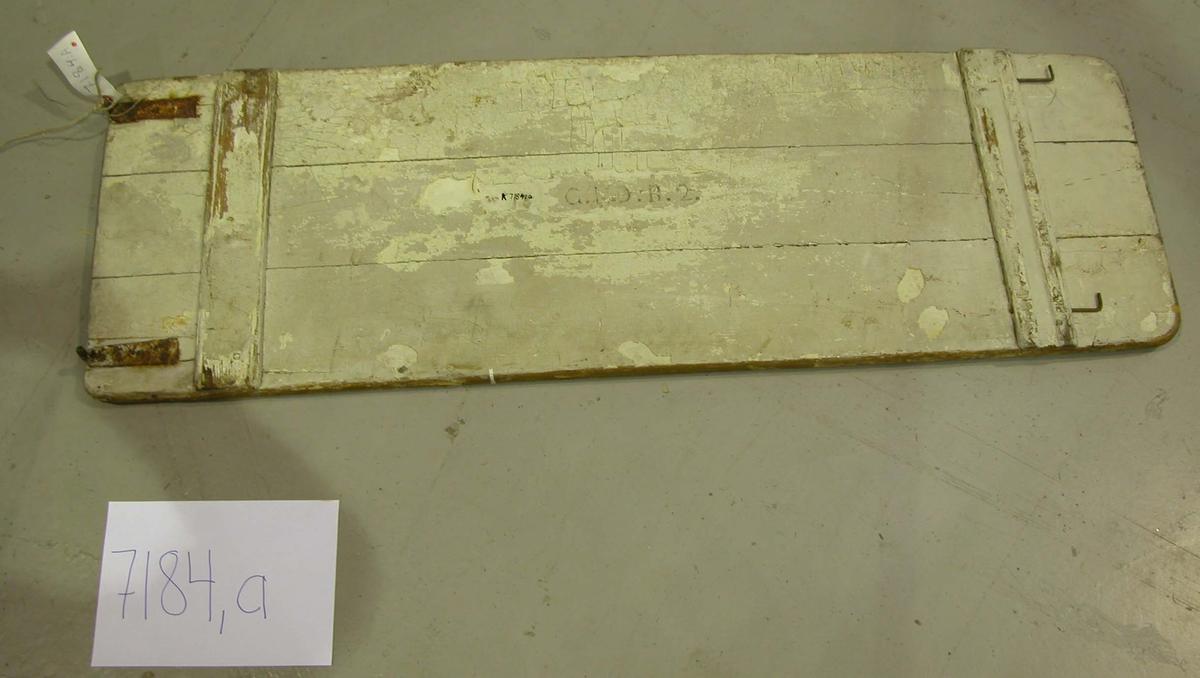 Backslagsbord tillverkat av tre spuntade bräder, på undersidan två tvärslåar. på ena kortsidan två plattjärnsbeslag, utsmidda runda i ena änden och bockade i vinkel. översdidan gulmålad undersidan brunmålad. Märkning: G.L.S.B 2.
