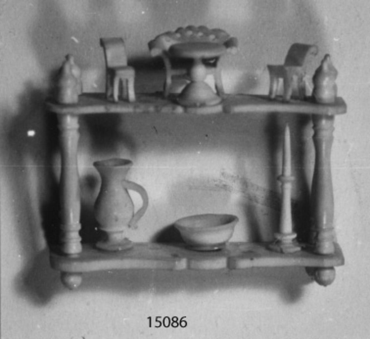 Scrimshaw (modell av atentienne). Sjömansarbete i ben i form av en atenienne med dockmöbler, kanna, skål och ljusstake.