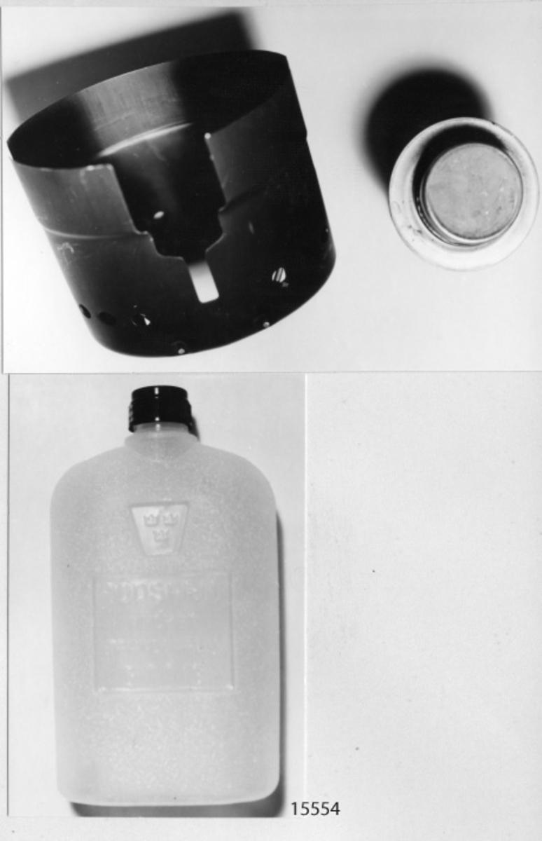 Spritkök, enmans av aluminium, mässing och plast. Bestående av ett vindskydd med hållare för kokkärl i svart eloxerad aluminium och en brännare för rödsprit (cylindrisk) samt en flaska av plast, avsedd för rödsprit.