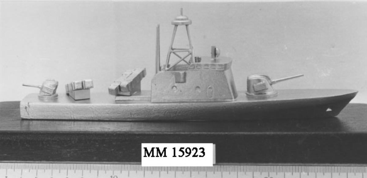 Modell av torpedbåt, typ Spica, Båten är silverfärgad. På fördäck sitter en kanon liksom en på akterdäck. Bakom överbyggnaden är två robotramper placerade, en åt styrbord och en åt babord. Hela modellen är påklistrad på en bottenplatta av mörkbrun mahogny.