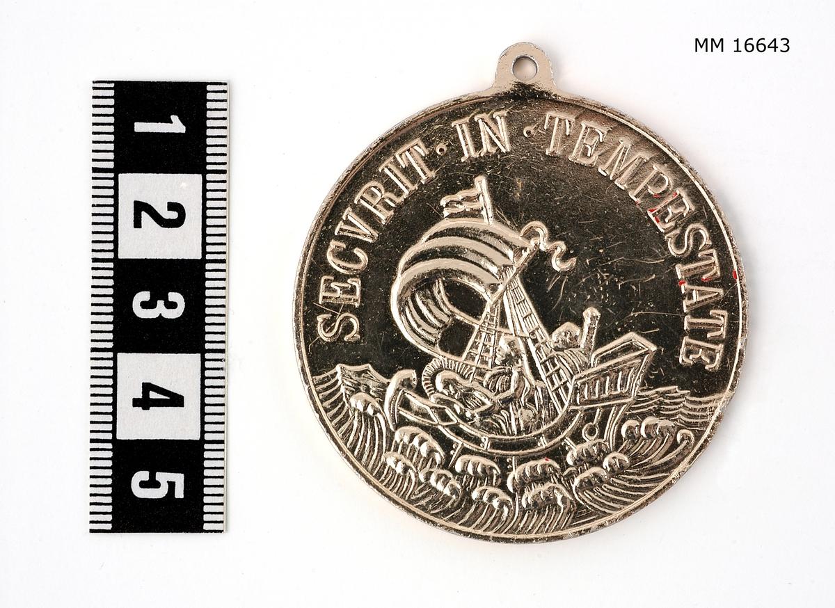 """Präglad, upphöjd relief på båda sidor av medaljen. På ena sidan ser man en häst med S:t Göran i rustning, i profil. Under hästen en drake vars huvud genomborras av ryttarens lans. Längs nedre kanten syns marken. I en halvcirkel längs övre kanten står skrivet i upphöjd relief: """" S.GEORGIVS_ EQVITUM_PATRONUS """". Den andra sidan visar ett fartyg från sidan, vindfyllt segel, tre personer varav en i fören har gloria. Under fartyget syns upprörda vågor. I en halvcirkel, längs övre kanten står skrivet i upphöjd relief: """" SECURIT_IN_TEMPESTATE """". Kanten buktar ut ( 0,5 cm ) med ett hål för upphängning."""